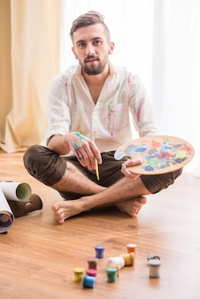 Jeune artiste est assis sur le sol avec des peintures.