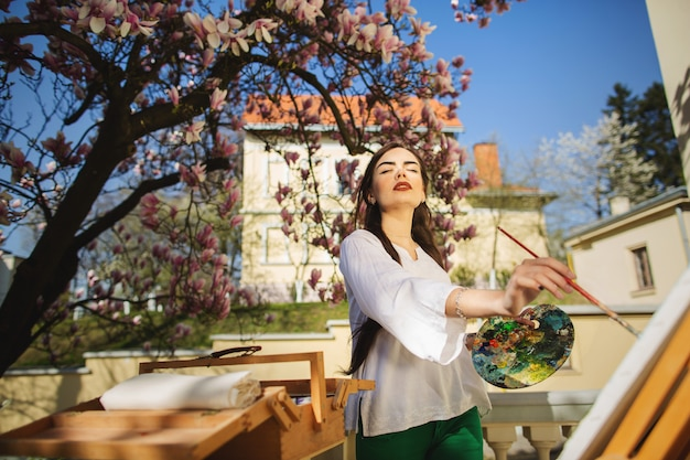 Jeune artiste femme brune tenant dans les mains un pinceau et une palette.