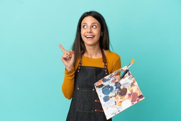 Jeune artiste femme caucasienne tenant une palette isolée sur fond bleu dans l'intention de réaliser la solution tout en levant un doigt vers le haut