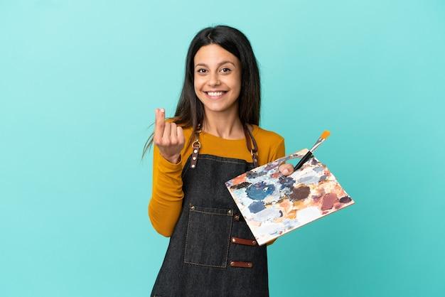 Jeune artiste femme caucasienne tenant une palette isolée sur fond bleu faisant un geste d'argent