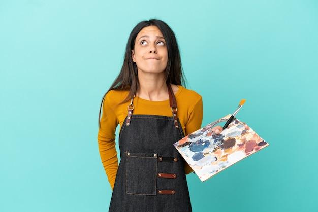 Jeune artiste femme caucasienne tenant une palette isolée sur fond bleu et levant