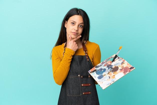 Jeune artiste femme caucasienne tenant une palette isolée sur fond bleu pensant