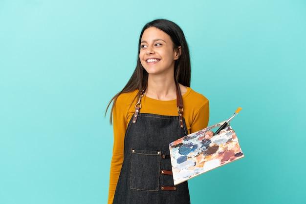 Jeune artiste femme caucasienne tenant une palette isolée sur fond bleu regardant sur le côté et souriant