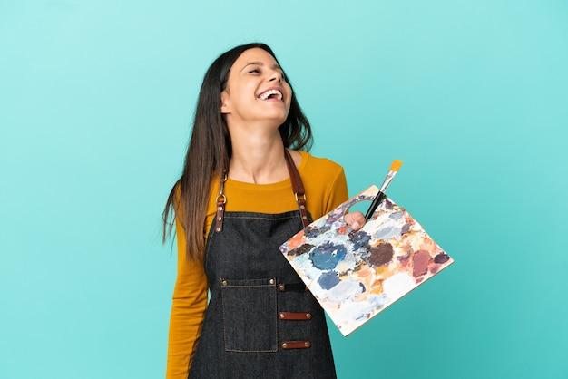 Jeune artiste femme caucasienne tenant une palette isolée sur fond bleu en riant