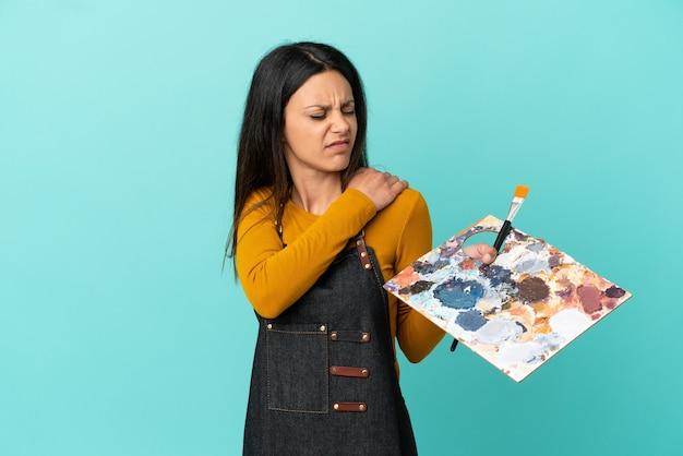 Jeune artiste femme caucasienne tenant une palette isolée sur fond bleu souffrant de douleurs à l'épaule pour avoir fait un effort