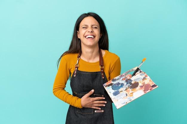 Jeune artiste femme caucasienne tenant une palette isolée sur fond bleu souriant beaucoup