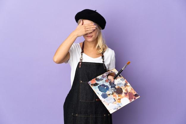 Jeune artiste femme russe tenant une palette isolée sur fond violet couvrant les yeux à la main. je ne veux pas voir quelque chose