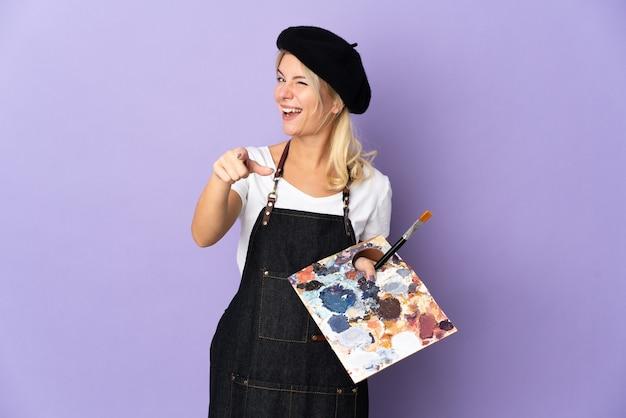 Jeune artiste femme russe tenant une palette isolée sur fond violet pointant vers l'avant avec une expression heureuse