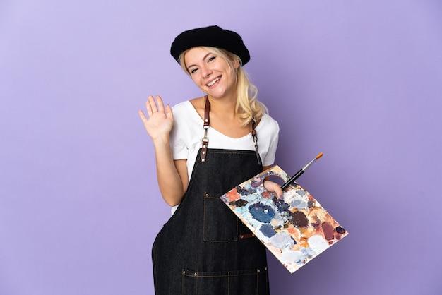 Jeune artiste femme russe tenant une palette isolée sur violet saluant avec la main avec une expression heureuse