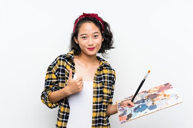 Jeune artiste femme tenant une palette sur fond blanc isolé avec le pouce levé parce que quelque chose de bien s'est passé