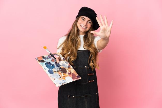 Jeune artiste femme tenant une palette isolée sur rose comptant cinq avec les doigts