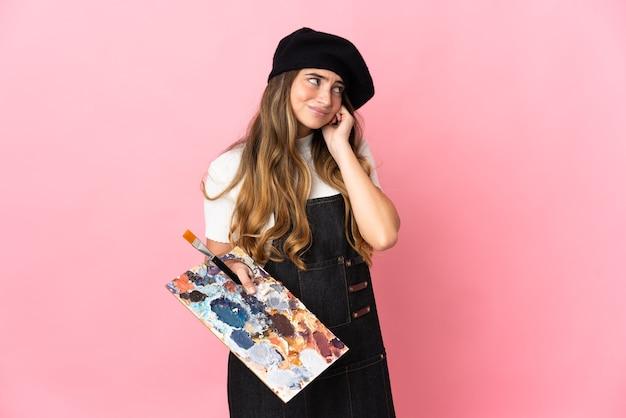 Jeune artiste femme tenant une palette isolée sur rose frustré et couvrant les oreilles