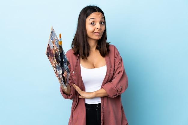 Jeune artiste femme tenant une palette isolée