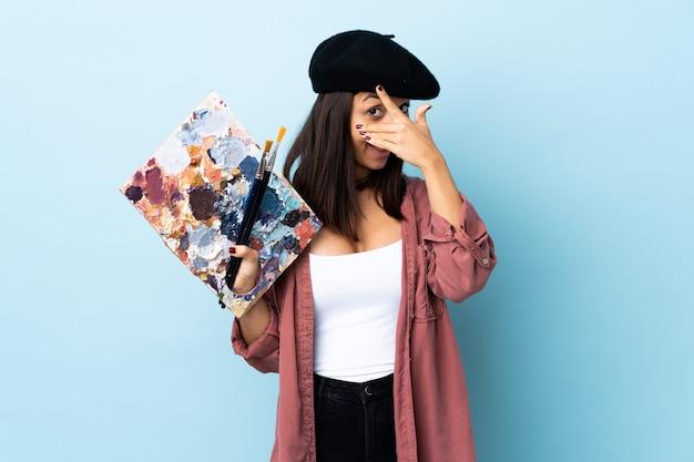 Jeune artiste femme tenant une palette sur un mur bleu isolé couvrant les yeux par les mains et souriant