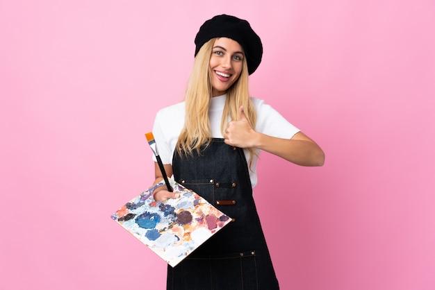 Jeune artiste femme tenant une palette sur un mur rose donnant un geste du pouce levé