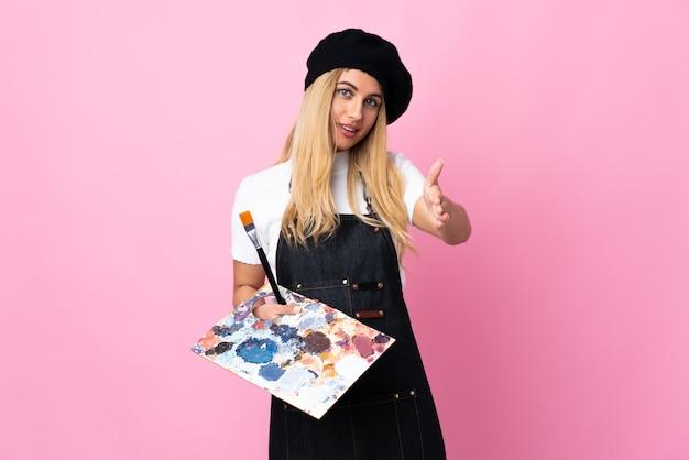 Jeune artiste femme tenant une palette sur poignée de main rose isolé après une bonne affaire