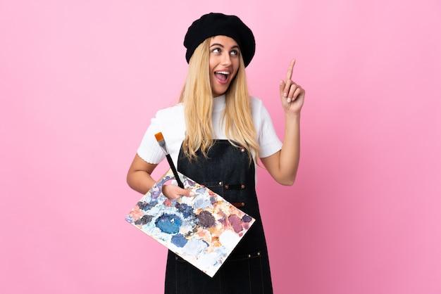 Jeune artiste femme tenant une palette sur rose isolé pointant avec l'index une excellente idée