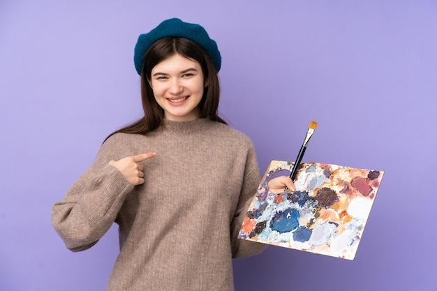 Jeune artiste fille tenant une palette sur un mur violet avec une expression faciale surprise