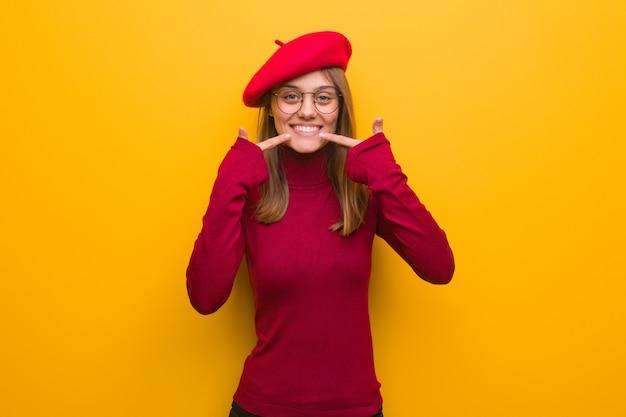 Jeune artiste française femme sourit, pointant la bouche