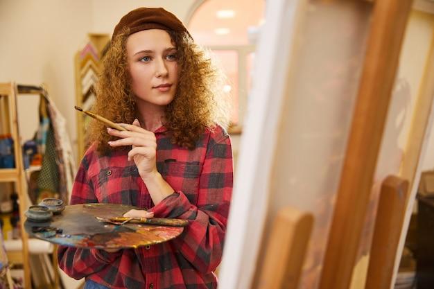 Jeune artiste frisé tient un pinceau et dessine une picrure