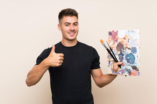 Jeune artiste homme sur un mur isolé avec le pouce levé parce que quelque chose de bien est arrivé