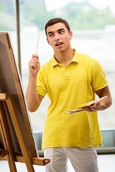 Jeune artiste masculin dessine des images en studio lumineux