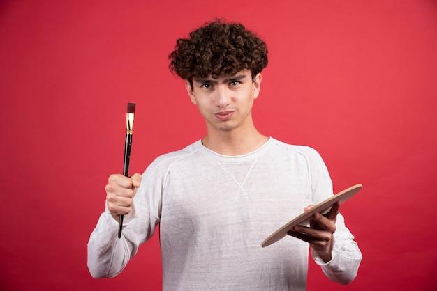 Jeune artiste masculin regardant la caméra avec des outils de peinture.