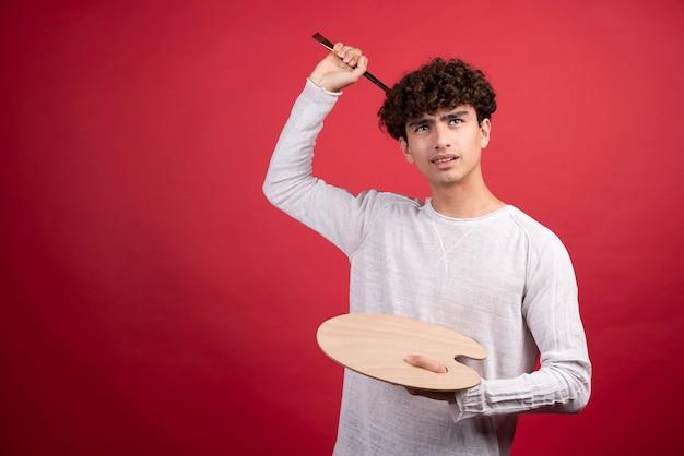 Jeune artiste masculin tenant la palette et les pinceaux.