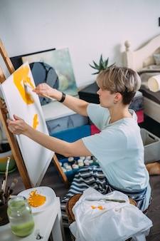 Une jeune artiste peint à la maison dans un studio de création