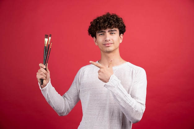 Jeune artiste pointant sur des pinceaux.