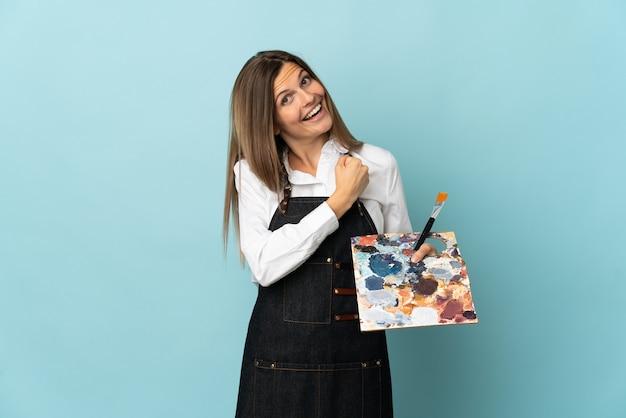 Jeune artiste slovaque femme isolée sur mur bleu célébrant une victoire