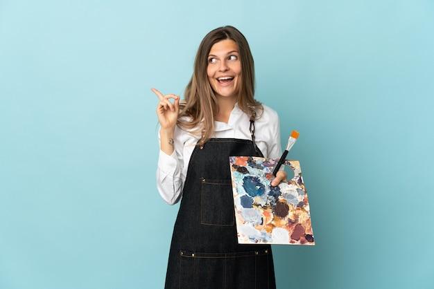 Jeune artiste slovaque femme isolée sur mur bleu dans l'intention de réaliser la solution tout en levant un doigt