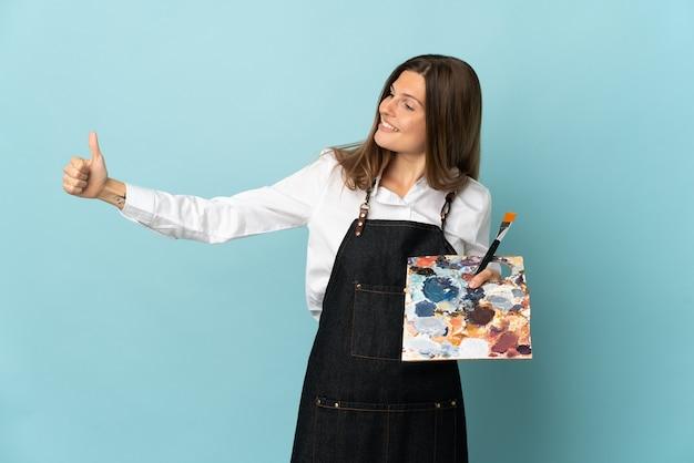 Jeune artiste slovaque femme isolée sur mur bleu donnant un geste de pouce en l'air
