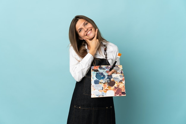 Jeune artiste slovaque femme isolée sur mur bleu heureux et souriant