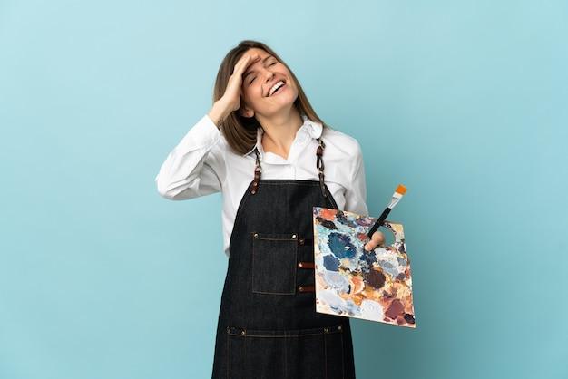 Jeune artiste slovaque femme isolée sur mur bleu souriant beaucoup