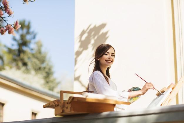Jeune artiste souriante de femme brune dresse un tableau dans la rue