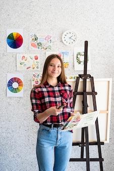 Jeune artiste tenant des pinceaux et des aquarelles dans son atelier