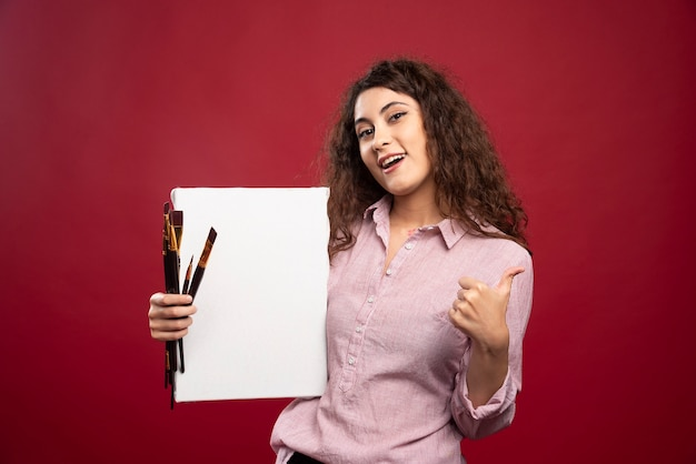 Jeune artiste tenant des pinceaux et de la toile donnant les pouces vers le haut.