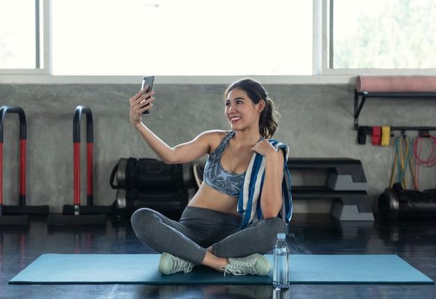 Jeune asiatique attrayant souriant fitness actif dans la salle de gym et prenant un selfie.