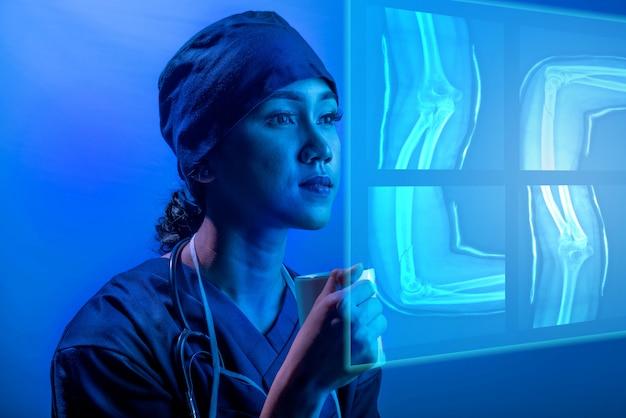 Jeune, asiatique, docteur, femme, regarder, numérique, ct, scan, sur, écran virtuel