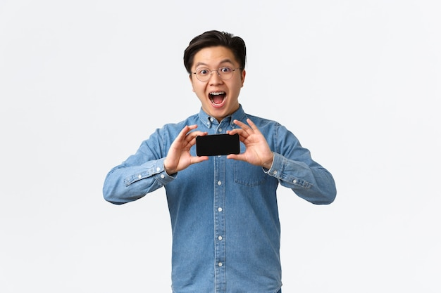 Un jeune asiatique étonné et excité à lunettes et à bretelles montrant un smartphone retourné horizontalement à l'int...