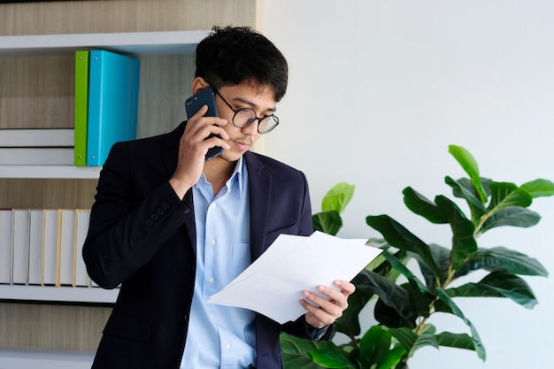 Jeune, asiatique, homme affaires, lecture, papiers, conversation, téléphone, bureau, communication affaires, et, technologie
