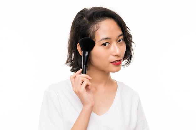 Jeune asiatique sur isolé avec pinceau maquillage