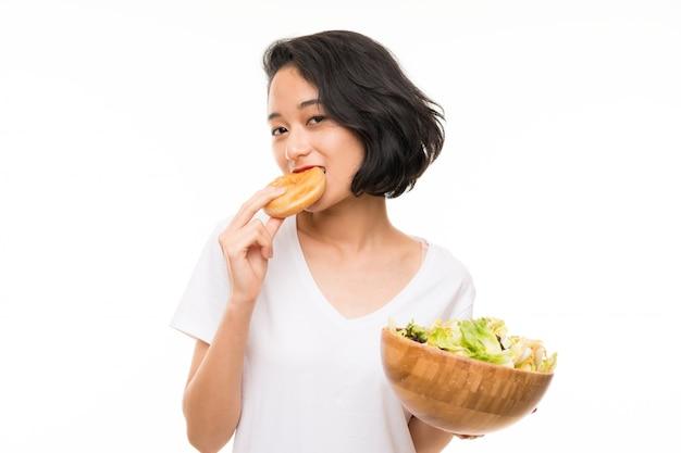 Jeune asiatique sur mur isolé avec salade et beignet