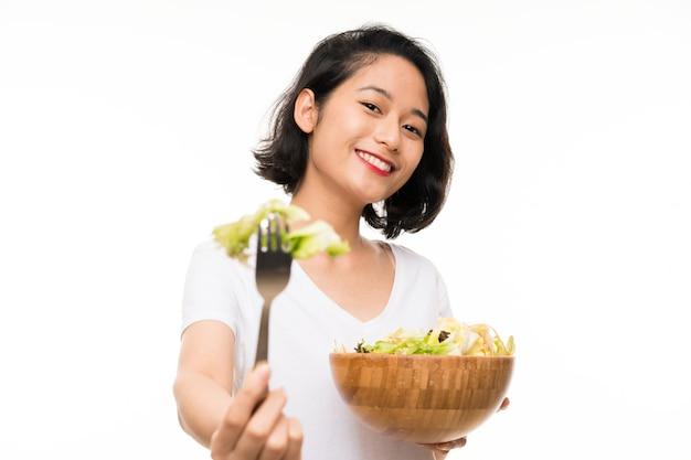 Jeune asiatique sur mur isolé avec salade