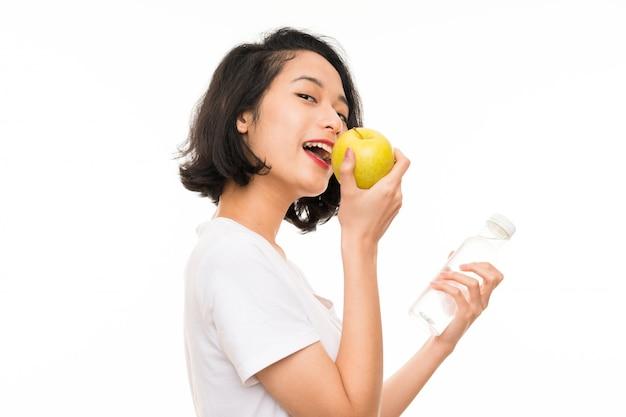 Jeune asiatique avec une pomme et une bouteille d'eau