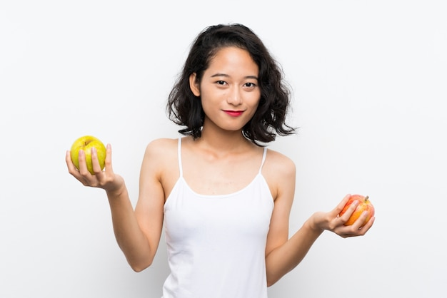 Jeune asiatique avec une pomme sur un mur blanc isolé