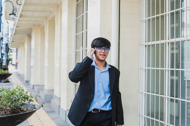 Jeune asiatique portant un costume noir et des lunettes parler au téléphone tout en souriant et en marchant