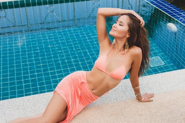 Jeune asiatique sexy belle femme en bikini rose, allongé à la piscine, peau mince et bronzée, accessoires glamour, bracelets, détendu, souriant, sensuel, vacances d'été, jambes