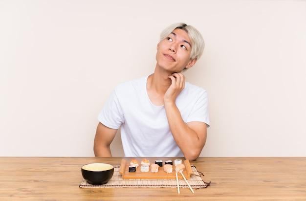 Jeune, asiatique, sushi, table, penser, idée